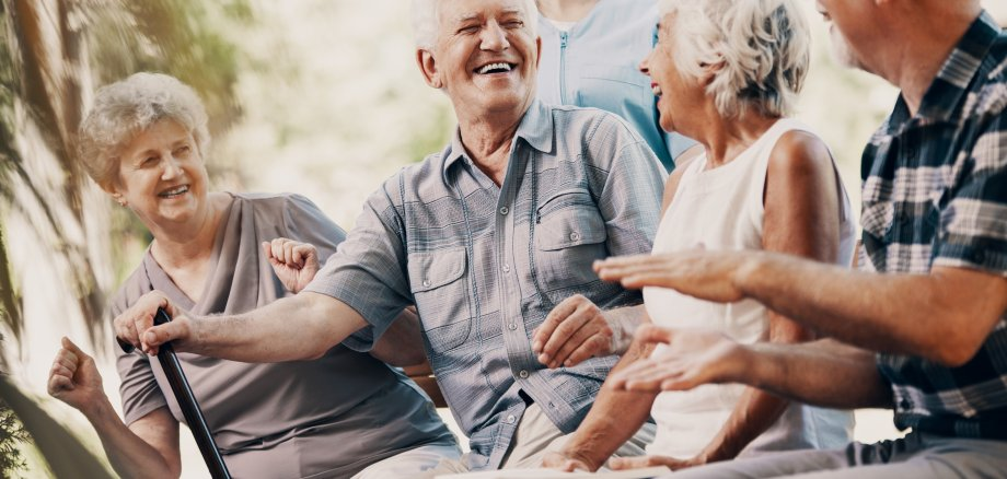 Happy elderly man with walking stick and smiling senior people relaxing in the garden